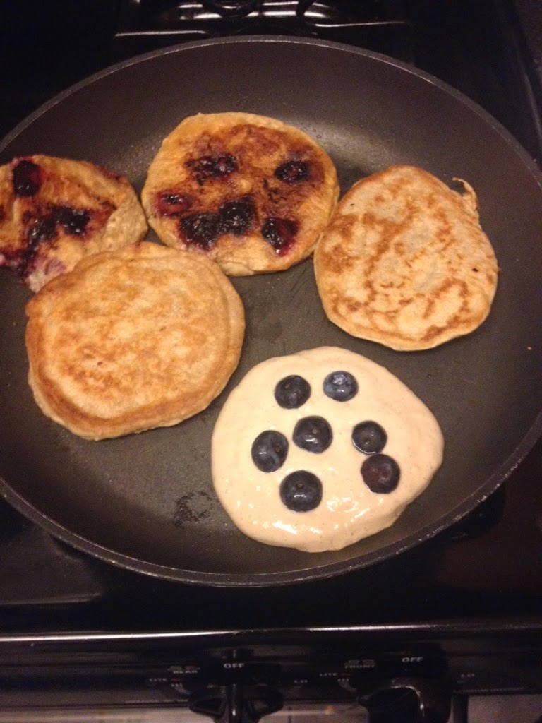 blueberry pancakes cooking on the griddle