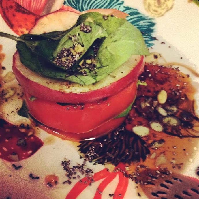 A perfectly stacked tomato and apple tower in a balsamic glaze on a plate with basil