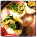 a plate odeviled eggs made with guacamole cut in halves on a plate