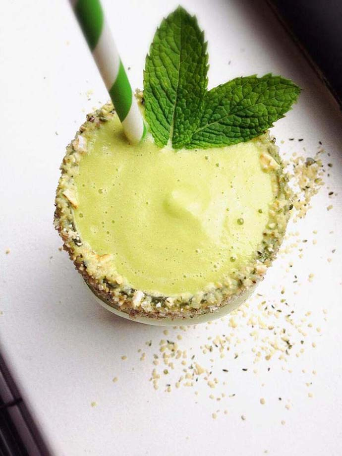 a lime green colored mint smoothie in a mason jar with a hemp seed crusted rim and mint leaves