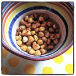 a handful of spicy crunchy chickpeas baked to perfection in a striped bowl
